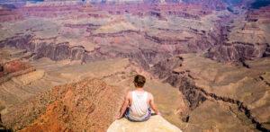 man sitting on ledge at Grand Canyon