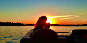 mom and child on pontoon boat on lake at sunset