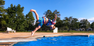 boy doing somersault from pool diving board