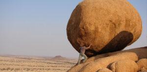 man pushing boulder in middle of desert